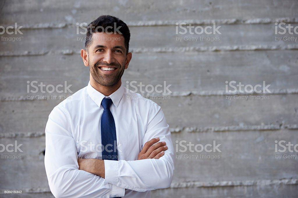 Hispanic homme daffaires debout contre le mur de bureau moderne