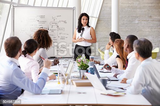 istock Hispanic Businesswoman Leading Meeting At Boardroom Table 504987356