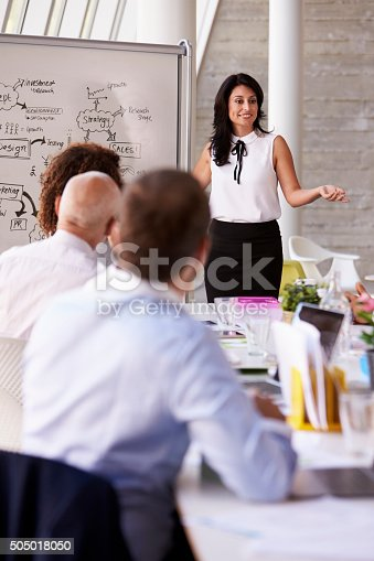 istock Hispanic Businesswoman Leading Meeting At Boardroom Table 505018050