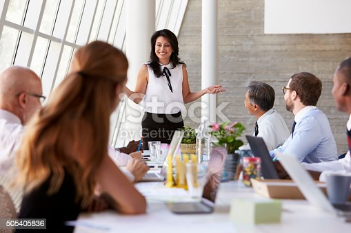 istock Hispanic Businesswoman Leading Meeting At Boardroom Table 505405836
