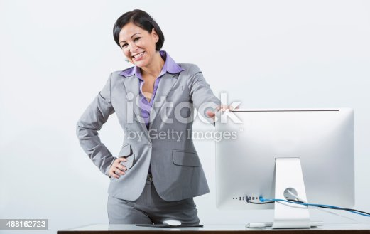1150572074istockphoto Hispanic businesswoman standing at desk with computer monitor 468162723