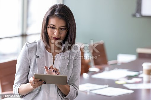 As she prepares for an important meeting, a young businesswoman uses a digital tablet to consult with a colleague via video conference.
