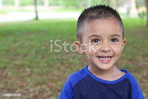 Hispanic child smiling in the park.