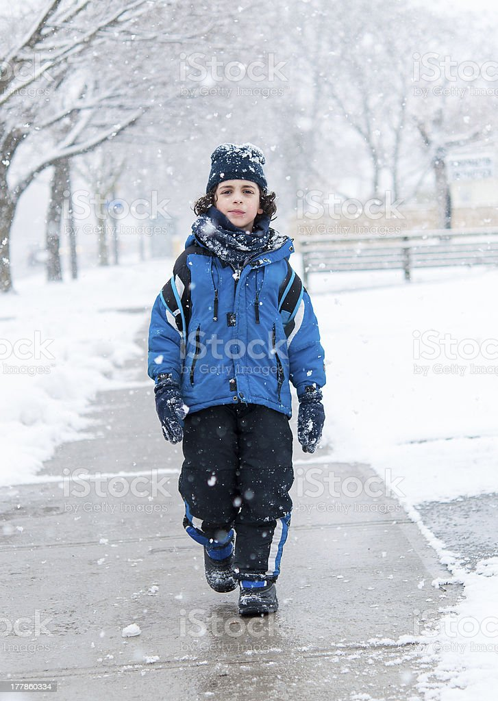 Hispanic Child Walking in the Sidewalk on a Snowy Day royalty-free stock photo