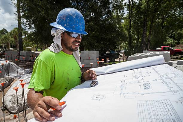 Hispanic Construction Supervisor Reviews Plan on Job Site Wide Angle stock photo