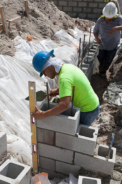 Hispanic Construction Workers Building Cinder Block Wall stock photo