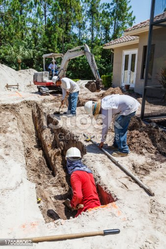 A four man crew of Hispanic construction workers operates a small backhoe and put the finishing touches on a trench.  It will be used to pour concrete into for footers at a job site in Southwest Florida.