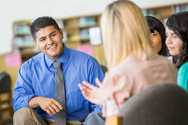 hispanic counselor discussing something during group therapy session - school counselor stock photos and pictures