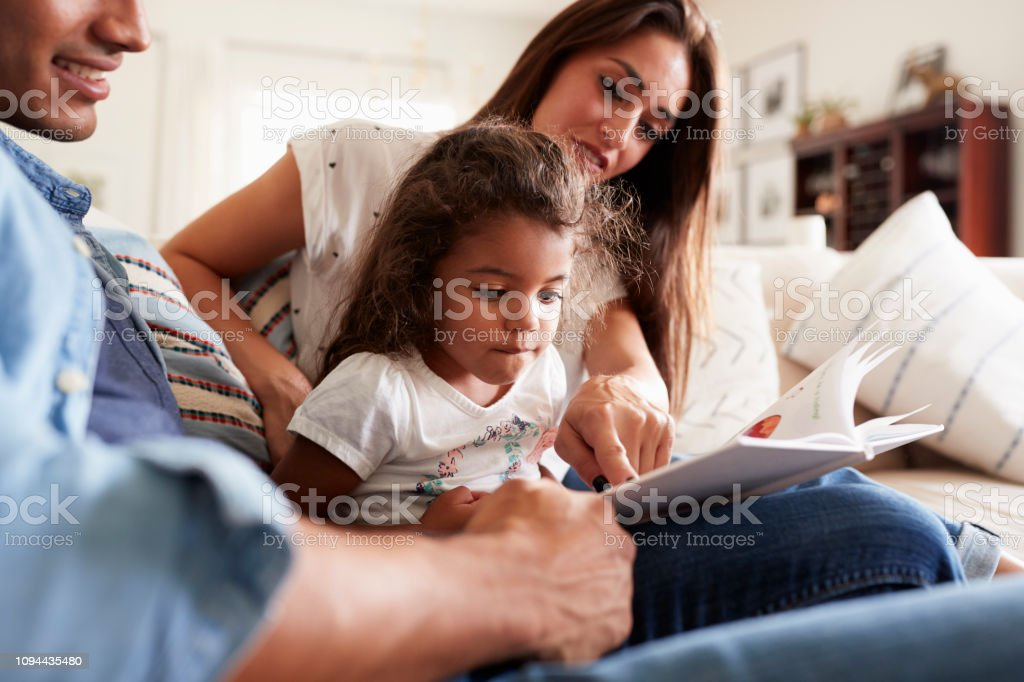 Hispanic couple and their young daughter sitting on the sofa reading a book together at home royalty-free stock photo