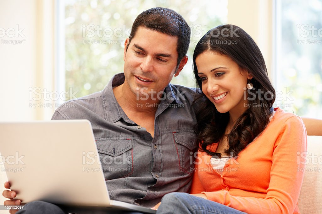 Hispanic couple at home with laptop stock photo