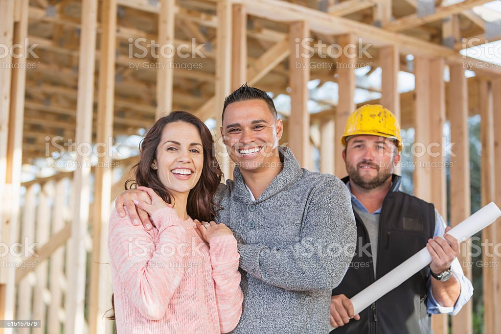 A happy Hispanic couple at the construction site of their new home,...