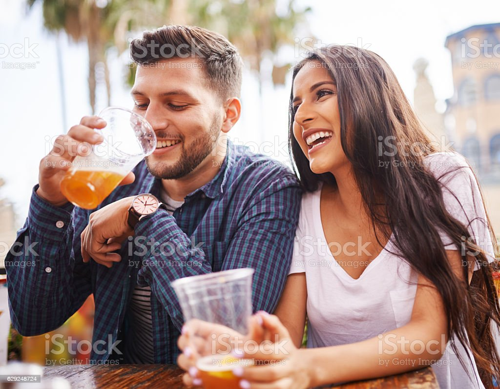 hispanic couple drinking beer on date together at outdoor patio stock photo