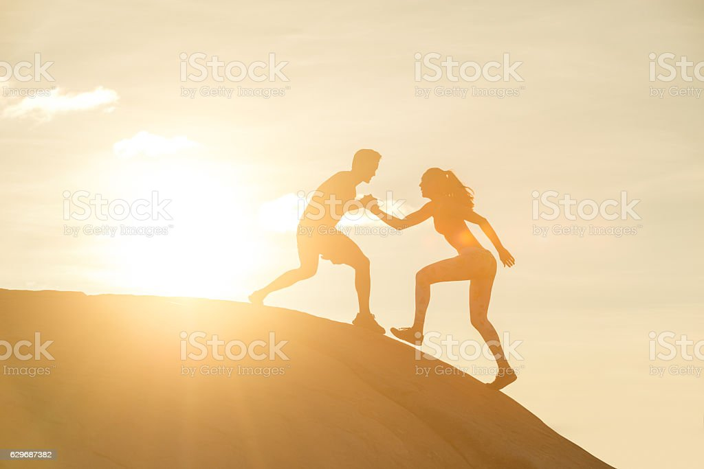 Hispanic Couple Helping Hands Silhouette Sunset stock photo