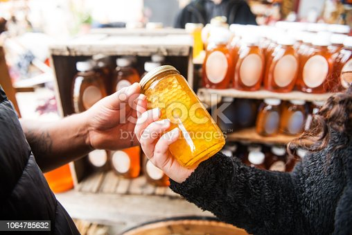 A Hispanic couple in their 20s shops for honey at a farmer's market in upstate New York.
