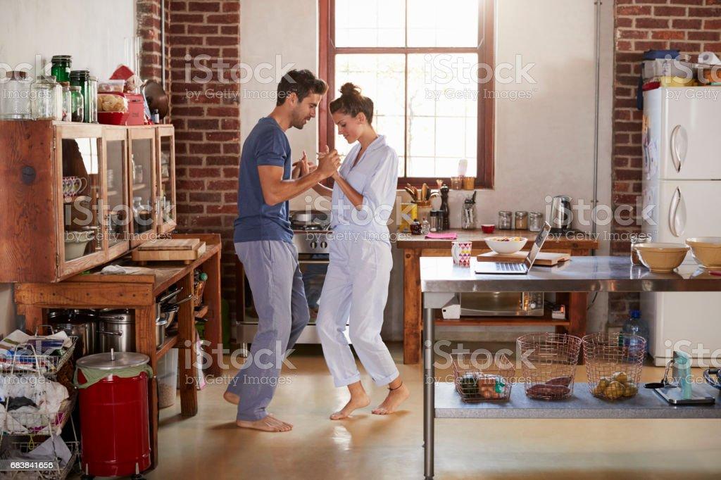 Hispanic couple in pyjamas dancing in kitchen, full length stock photo