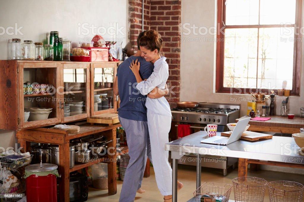 Hispanic couple in pyjamas embracing in kitchen stock photo