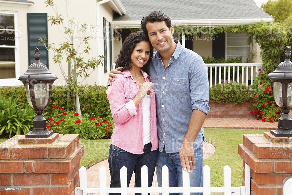 Hispanic couple outside new home stock photo