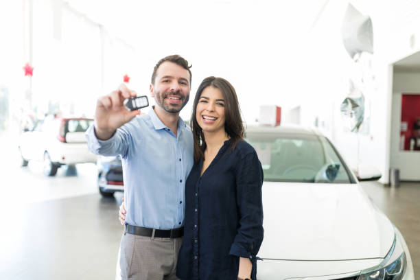 Hispanic Couple Showing Off New Car Keys With Pride Cheerful Latin man and woman smiling while showing off their new car keys in showroom status symbol stock pictures, royalty-free photos & images