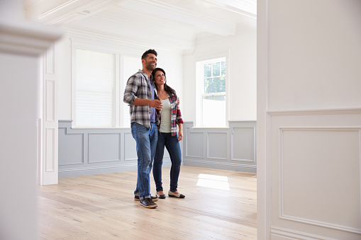 Hispanic Couple Viewing Potential New Home Stock Photo - Download Image Now