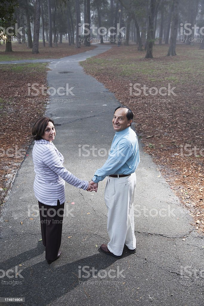 Hispanic couple walking in park royalty-free stock photo