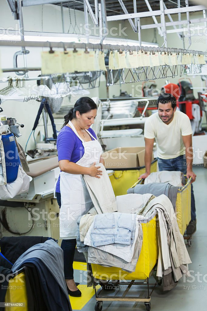 Hispanic couple working in dry cleaner stock photo