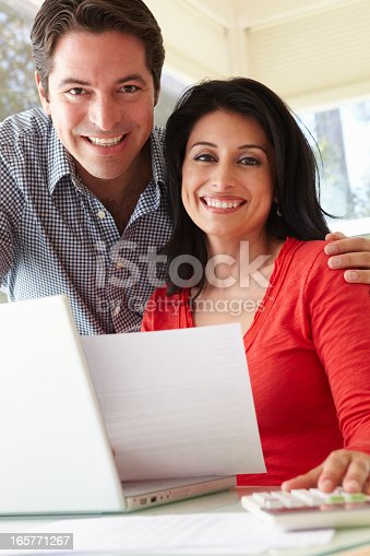 istock Hispanic Couple Working In Home Office 165771267