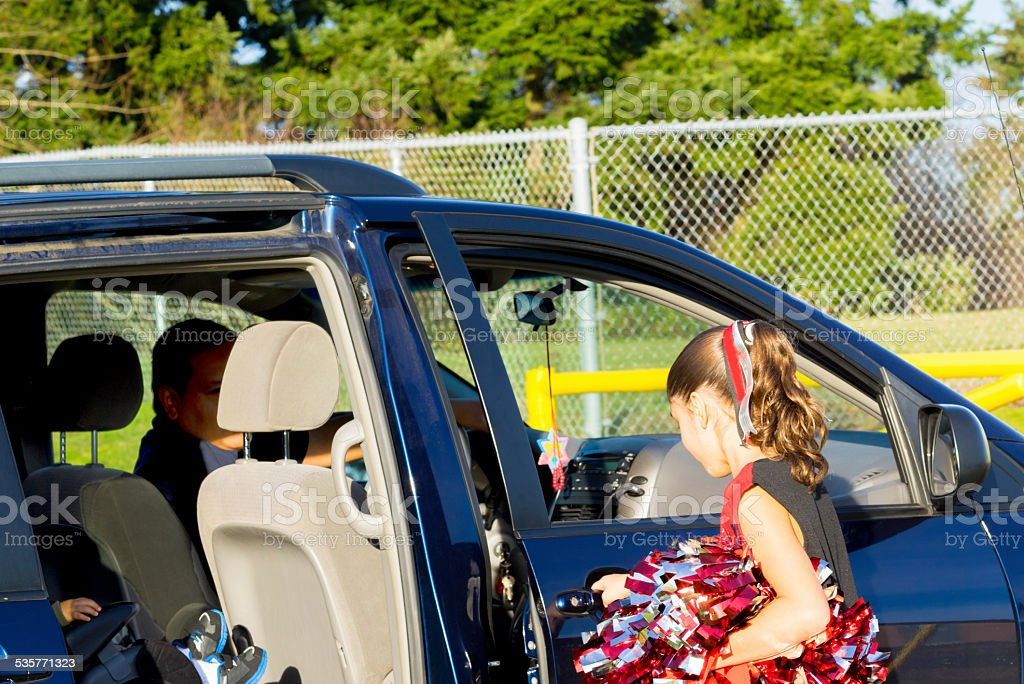 Hispanic Dad Picks Up Daughter After Cheerleader Practice stock photo