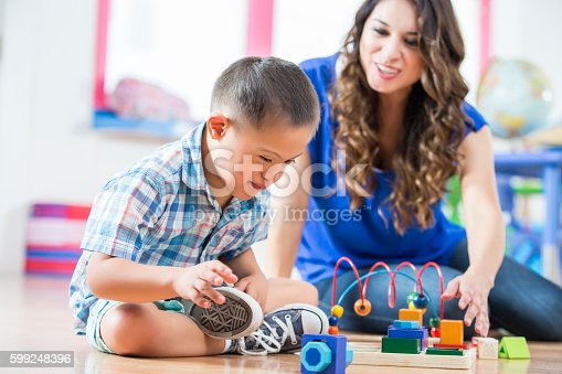 istock Hispanic Down Syndrome boy reaching for toys at daycare center 599248396