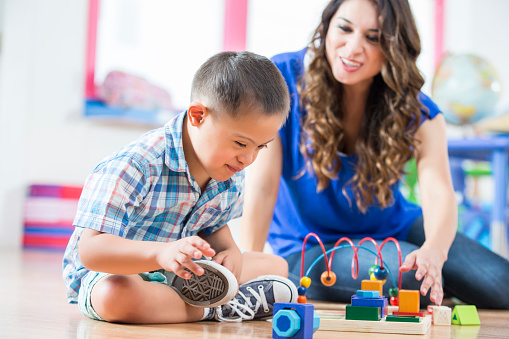 Hispanic Down Syndrome Boy Reaching For Toys At Daycare Center Stock Photo - Download Image Now
