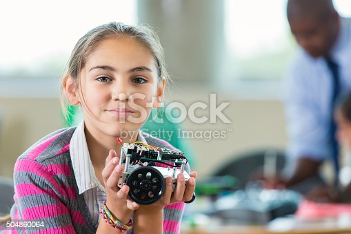istock Hispanic elementary girl building robot during after school science club 504860064