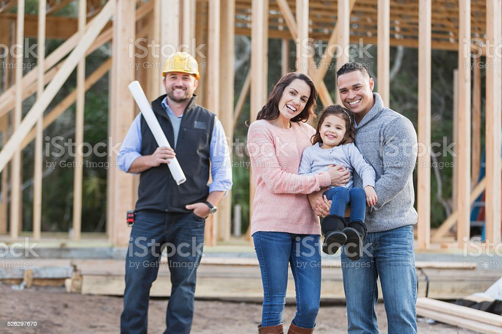 Hispanic family building a new home, with contractor stock photo