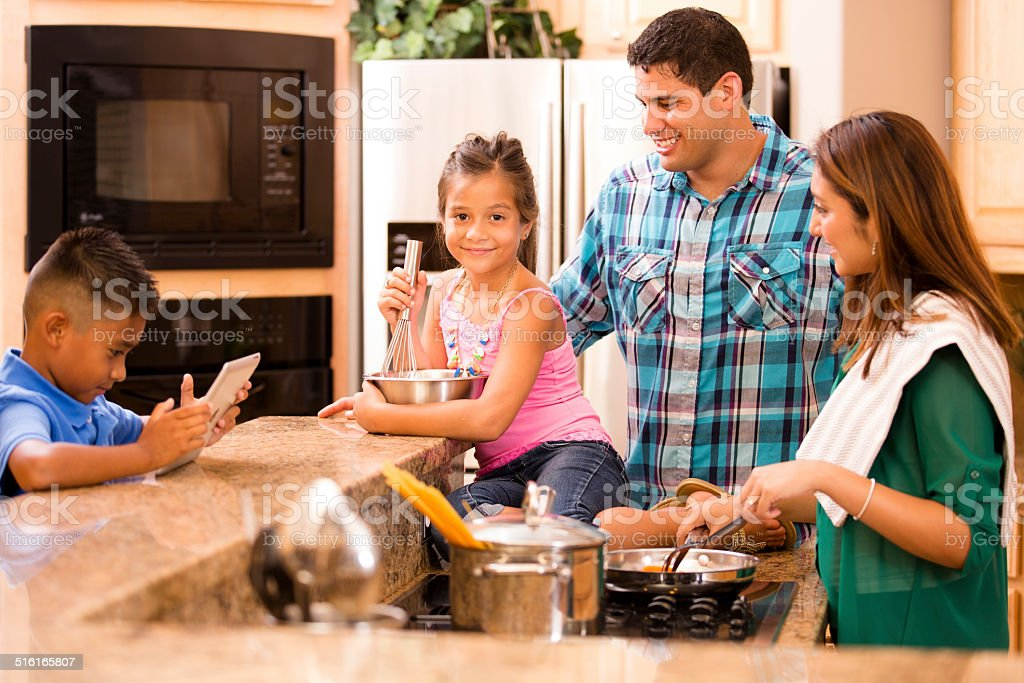 Hispanic family cooking dinner together in home kitchen. stock photo