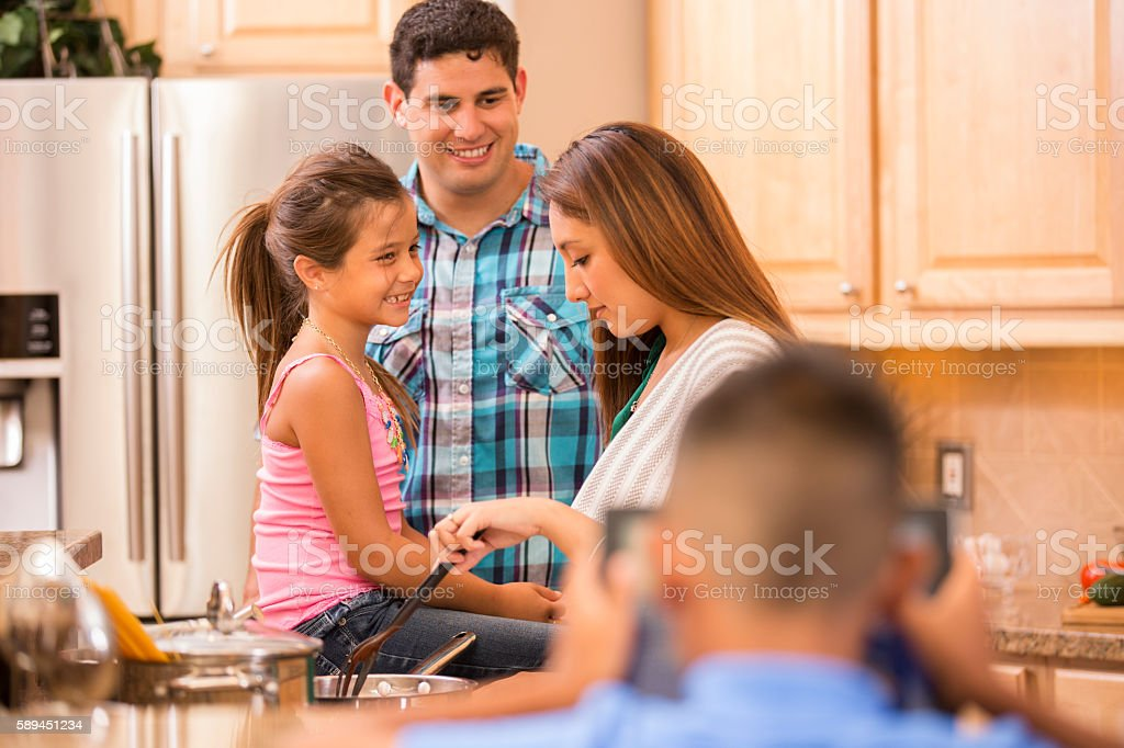 Hispanic Family Cooking Dinner Together In Home Kitchen Royalty Free Stock Photo