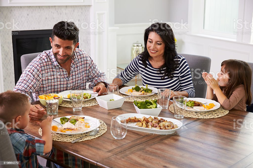 Hispanic Family Enjoying Meal At Table stock photo