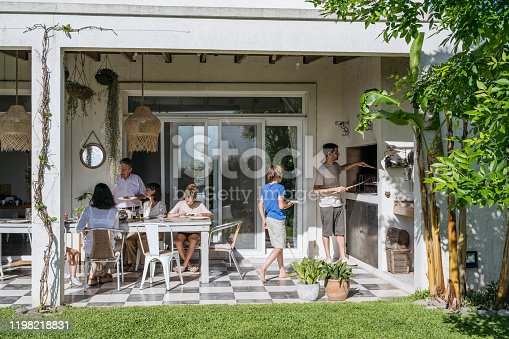 Multi-generation Argentine family seated at outdoor dining table while traditional asado midday meal is prepared.