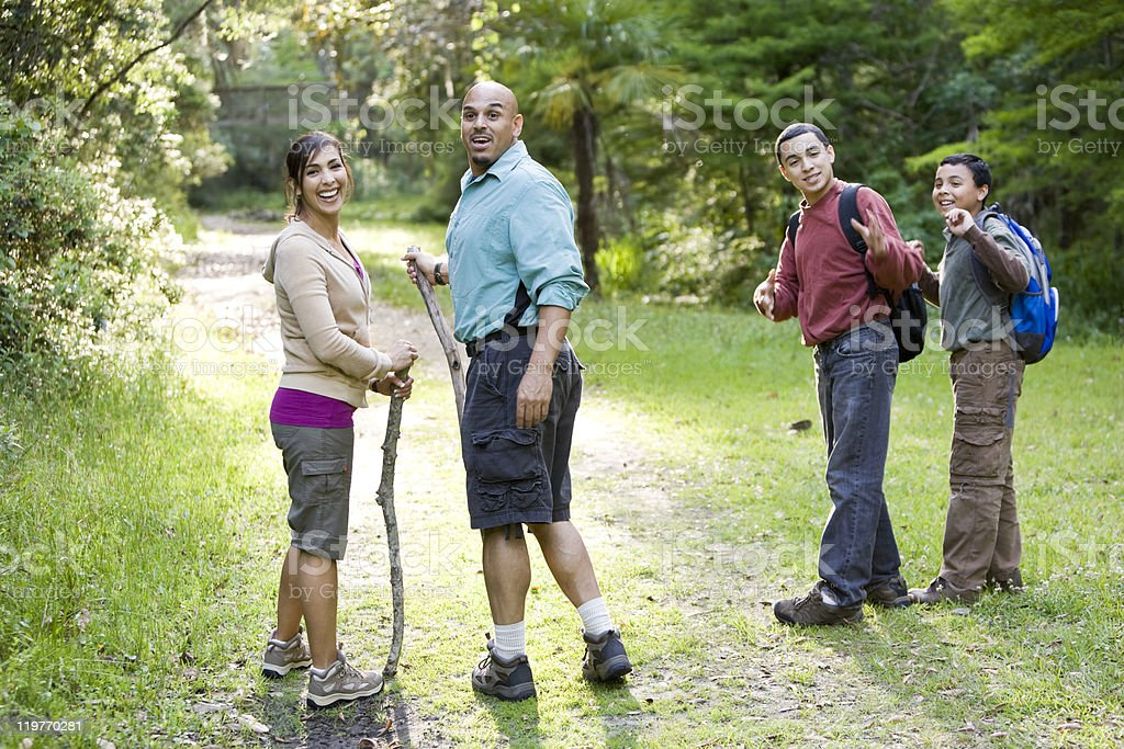 Hispanic family hiking in woods on trail royalty-free stock photo
