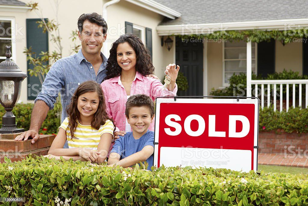 Hispanic family outside home with sold sign stock photo