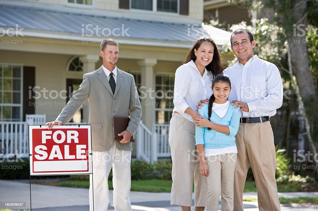 Hispanic family outside house for sale with real estate agent royalty-free stock photo