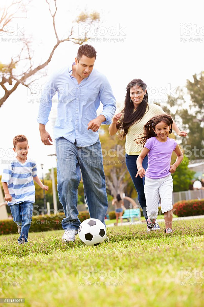 Hispanic Family Playing Soccer Together stock photo