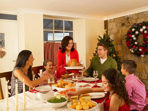 Hispanic family serving Christmas dinner stock photo