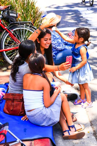 hispanic family sit on the sidewalk taking selfies in santa barbara, ca, usa - family 4th of july zdjęcia i obrazy z banku zdjęć