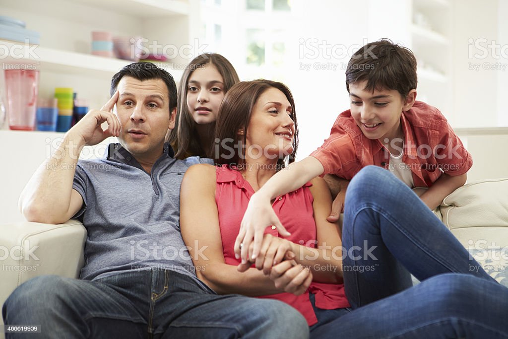 Hispanic Family Sitting On Sofa Watching TV Together royalty-free stock photo