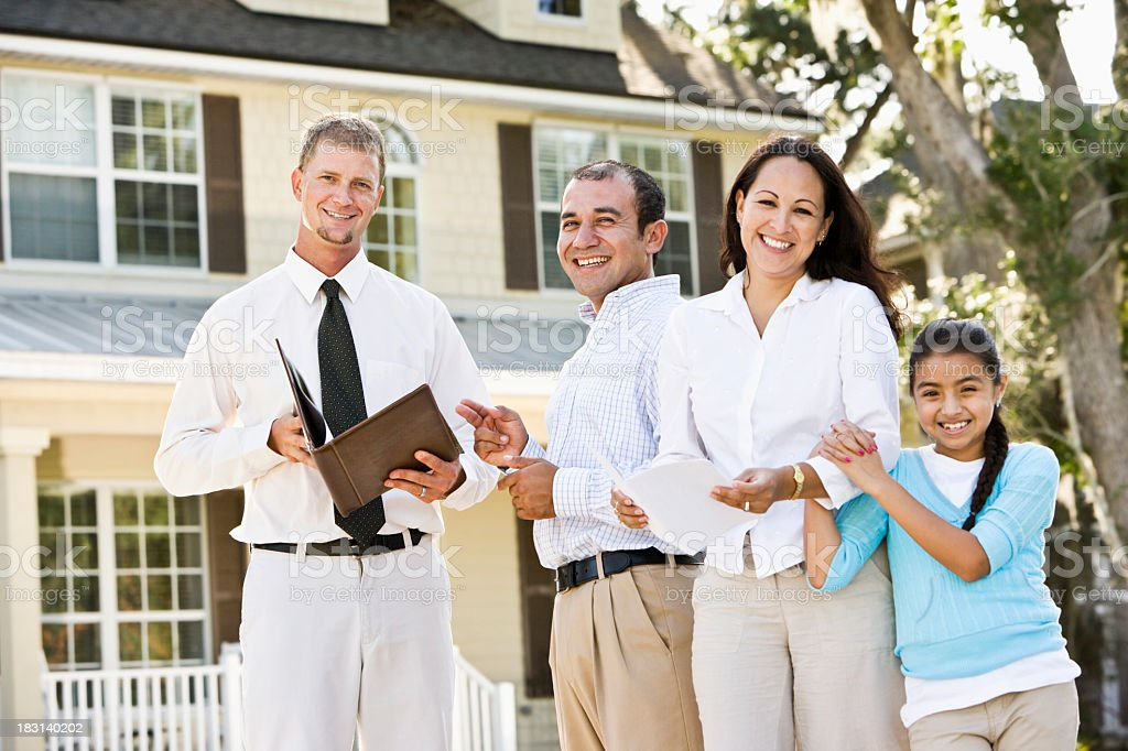 hispanic family with real estate agent in front of house