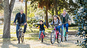 An Hispanic family with two children riding bicycles together in a city park on a sunny autumn day. The little 6 year old boy has a big grin on his face, riding in the middle between his parents and 10 year old sister.