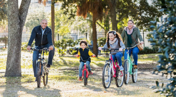 Hispanic family with two children riding bikes stock photo