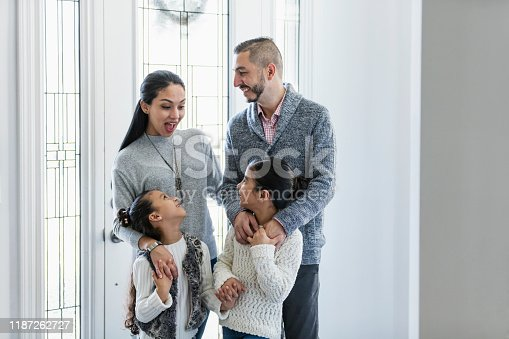 670900812 istock photo Hispanic family with two girls, by front door 1187262727