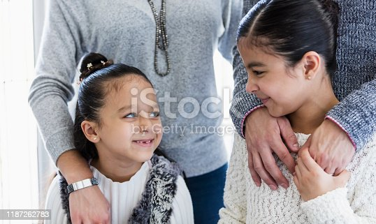 670900812 istock photo Hispanic family with two girls smiling at each other 1187262783