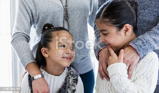 670900812 istock photo Hispanic family with two girls smiling at each other 1187262791