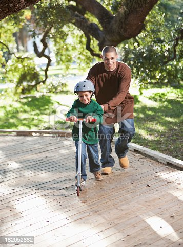 665192886 istock photo Hispanic father and boy on scooter in park 182052662
