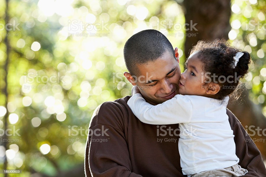 Hispanic father and daughter hugging at park stock photo